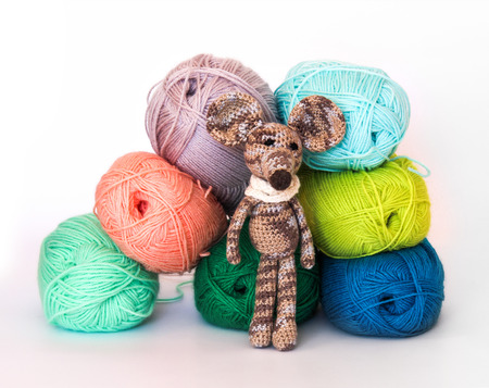 childrens playing: small colorful knitted toy mouse in a white scarf playing with colored yarn, threads of wool, Bright childrens toy, clew, knitted mouse between skeins