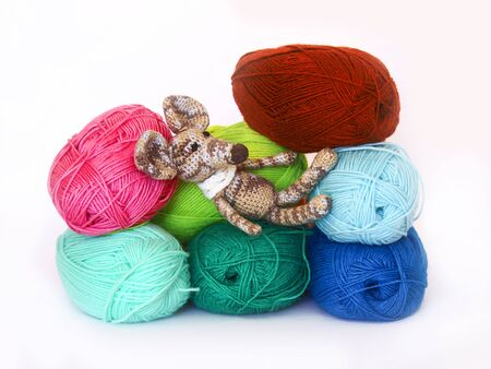 childrens playing: small colorful knitted toy mouse in a white scarf playing with colored yarn, threads of wool, Bright childrens toy, clew