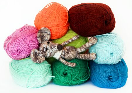clew: small colorful knitted toy mouse in a white scarf playing with colored yarn, threads of wool, Bright childrens toy, clew