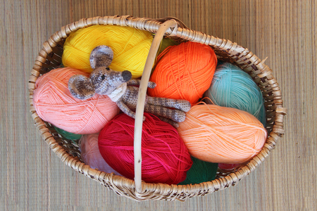basket embroidery: knitted toy mouse is mottled in a wicker basket among the skeins of wool,