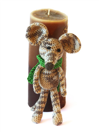 mouse hole: small colorful knited Bright childrens toy mouse model in a green scarf from colored yarn, threads of wool clew, Mouse rolls a dark brown candle into the hole Stock Photo
