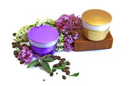 feminine beauty: jar natural cream sprig bloom purple white lilac roasted coffee beans tar soap cosmetic scrub set isolated on white background. Feminine, beauty and cosmetics concept, green branch of medical kolanhoe