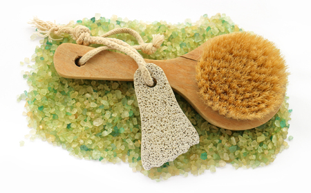 revitalizing: stripe background of large salt crystals colorful yellow green bath with juniper spa pumice in the form of a foot with a rope, brush massage Stock Photo