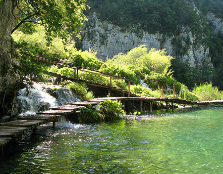Reserve Park Plitvice Lakes, Croatia, hiking trail on the lake along the waterfalls. Water drops glisten in the sun. Illustration
