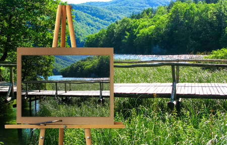 glisten: Easel with a painting watercolor Reserve Park Plitvice Lakes, Croatia, hiking trail on the lake along the waterfalls. Water drops glisten in the sun. Illustration. Photo manipulation concept.