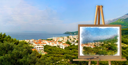 mediterranean: blurred background and a picture on an easel in the foreground watercolor painting of Mediterranean bay indoor mountain range with coastal homes. Photo manipulation concept. Stock Photo