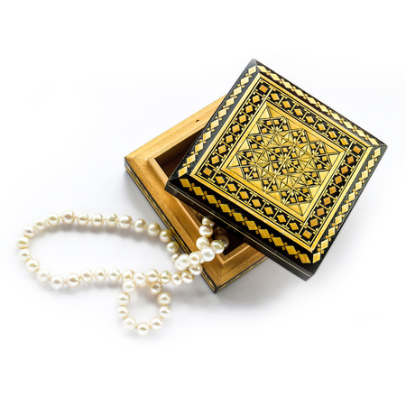 carved wooden box and pearl strand isolated