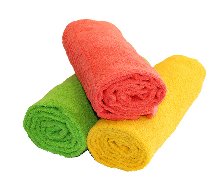 Yellow, green and red towels rolled up isolated