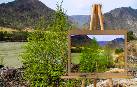 Easel with a painting watercolor illustration of Altai Mountains on a canvas on a landscape.  Lost settlement, road. Photo manipulation concept. Stock Photo