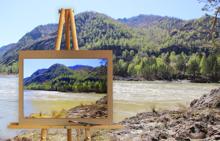 Easel with a painting watercolor illustration of Altai Mountains on a canvas on a landscape.   Photo manipulation concept. Stock Photo