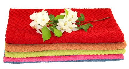 A pile of colorful towels, a sprig of white apple flowers and green leaves on a white background