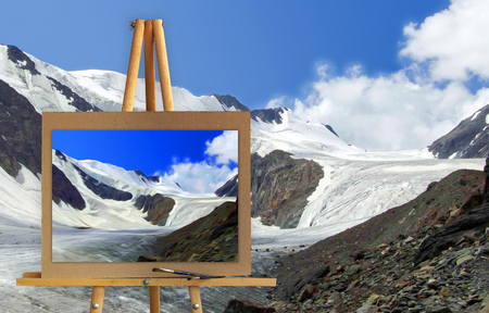 Easel with a painting watercolor landscape of high mountains with peaks covered by snow at winter  Photo manipulation concept.