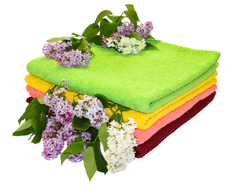absorbent: A pile of colorful towels, a sprig of white lilac flowers and green leaves on a white background
