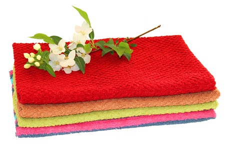 absorbent: A pile of colorful towels, a sprig of white apple flowers and green leaves on a white background