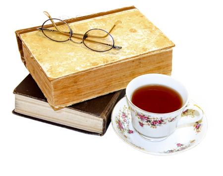 tea hot drink: On an old book with a torn binding, broken spine are glasses and a cup of tea isolated on white Stock Photo