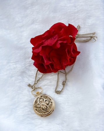 Flower red rose and gold filigree work clock - pendant with lid lay on white fur