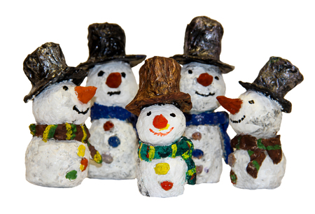 funny kids snowmen fashioned from papier-mache isolated on white, blurred image; covered with varnish shines in the sun Stock Photo