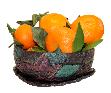 composition of bright orange mandarin fruit and faded leaves in a vintage papier-mache basket isolated Stock Photo