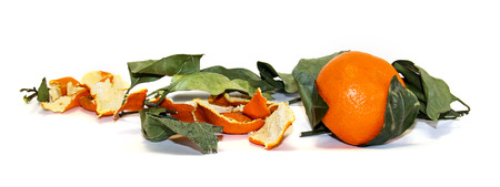 composition of bright orange mandarin fruit, skins and faded leaves isolated Stock Photo
