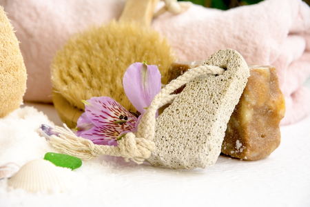 Sea salt crystals for bathroom, pumice, luff,  alstroemeria flower, body brush, shells, handmade soap with the addition of sand for heels Stock Photo