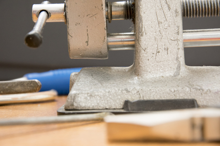 small portable vice screwdriver tools for repair  randomly scattered on the work surface