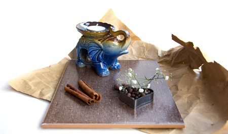 white candle in candlestick, elephant shape, branch  of flowers, heart form coffee beans, chocolate muffin, cinnamon sticks, cocoa. composition in brown and blue tones on crumpled wrapping paper 版權商用圖片