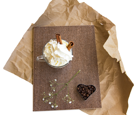 branch of flowers, heart form coffee beans, cinnamon sticks, whipped cream in a glass cup composition in brown tones on crumpled wrapping paper