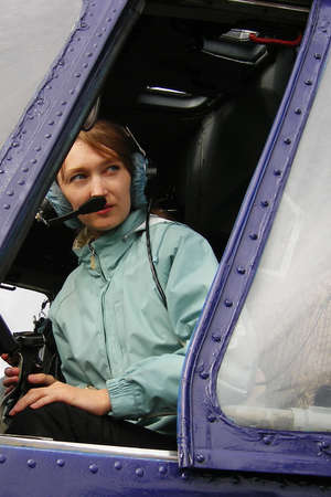 helicopter pilot: young woman is the pilot of helicopter ready to fly