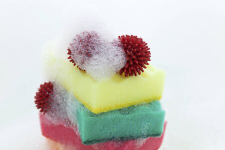 Multi-colored sponges and abstract coronavirus model in soapy foam.