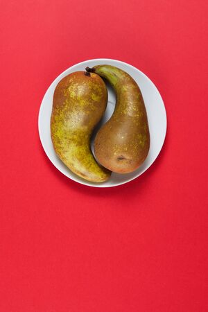 Yin and yang symbol - Two green pears on a white plate over red . Copy space. Stockfoto