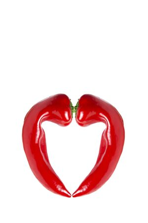 Heart-shaped pepper. Two ugly red peppers on a white background. Collage. Copy space. Vertical orientation.