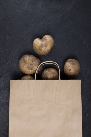 Food waste reduction. Using in cooking imperfect products. Refusal of plastic bags.  Ugly potatoes in a paper bag on a dark background. Closeup. Copy space. Stock Photo