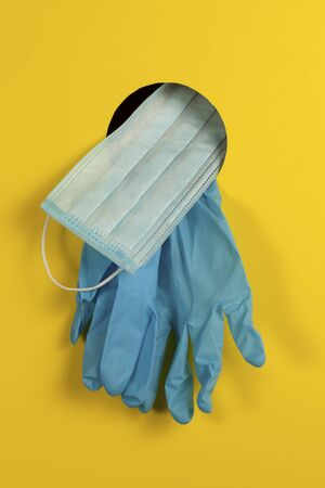 Medical concept. Disposable gloves and face mask through a hole on a yellow background as a means of protection against coronavirus infection nCov-2019. Closeup.