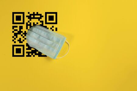 Protective face mask through a hole in a yellow background. Concept on the topic of quarantine and the introduction of a pass or Qr code to exit the house. Place for text. Stock fotó