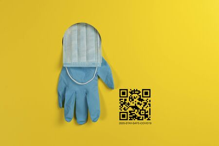 Disposable medical gloves and a protective face mask through a hole in a yellow background. Concept on the topic of quarantine and the introduction of a pass or Qr code to exit the house.