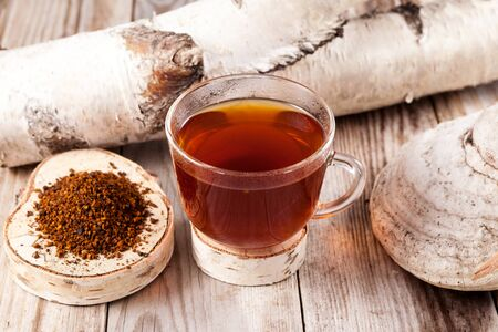 Chaga tea - a strong antioxidant, boosts immune system, has detox quality, improves digestive. A mug of healing drink is on the table next to a birch mushroom.