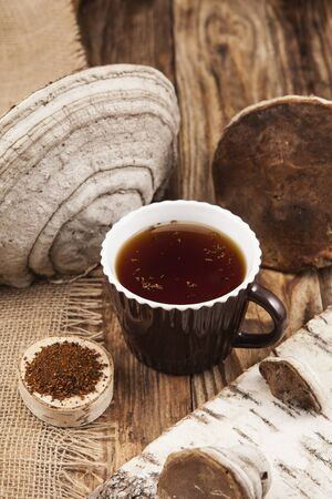 Chaga mushrooms infusion in cup on rustic wooden table. Healthy beverage. View from above. Vertical format.