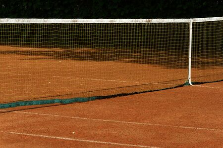Fragment of an outdoor clay tennis court. Grid and marking lines visible, selective focus.
