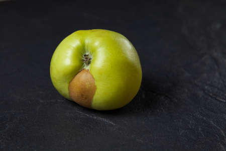 An ugly fruit. Green apple with a spot on a dark background. Concept - Food waste reduction. Using in cooking imperfect products.
