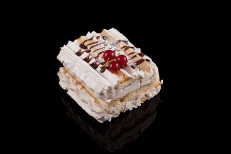 Delicious meringue cream dessert, garnished with currants and caramel syrup. Dark background with reflection, copy space.