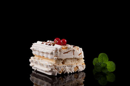Delicious dessert with meringue-based cream. Mint leaf. Dark background with reflection, copy space. 스톡 콘텐츠