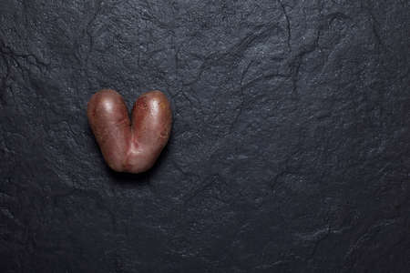 Ugly potato in the shape of a heart on a dark textured stone background. Concept - Reducing food waste. Vegetables and fruits of unusual shape are good for human consumption.
