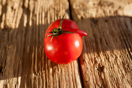 Ugly tomato on an old wooden board. Concept - eating vegetables and fruits that are imperfect in shape.