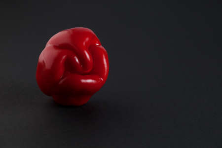 Ugly red bell pepper on dark background with copy space. Concept - reduction of food organic waste. Deformed, crooked vegetables and fruits can be eaten.