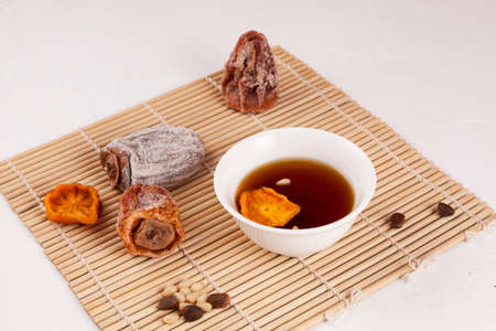 Sujeonggwa - Korean iced tea. Dark reddish brown in color, it is made from gotgam (dried persimmon) and ginger and is often garnished with pine nuts. Selective focus, copy space.