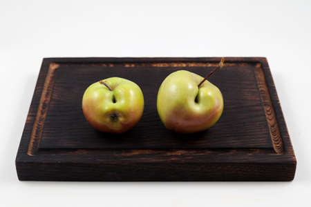 Ugly fruits. Two green apples with flaws on a dark wooden cutting board. Selective focus, copy space. Concept - Food waste reduction. Using in cooking imperfect products.