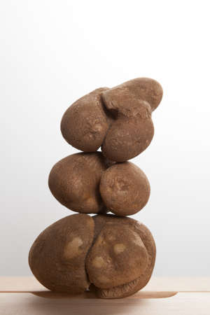 Ugly brown potatoes with deep cracks are stacked in the form of an abstract tree or pyramid. Close-up, selective focus. Concept-unusual vegetables and fruits. Reduce the amount of plant or food waste.