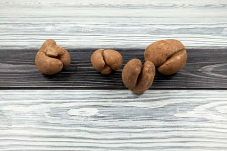 Ugly potatoes with deep cracks on a textured wooden background. Concept - unusual vegetables and fruits. Reduce the amount of plant or food waste.