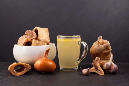 Homemade boiled beef bone broth in transparent cup on a dark background with meat and vegetables. Bones contain collagen.