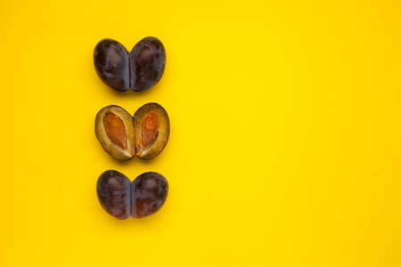 Fused fruits. Whole double prunes and half. Ugly fruits on a yellow background with copy space. Selective focus, copy space. Concept - Food waste reduction. Using in cooking imperfect products. 免版税图像
